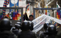 Police block supporters of former President Evo Morales from entering the area of Congress in La Paz, Bolivia, on Nov. 12, 2019. (AP Photo/Natacha Pisarenko)