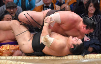 Yokozuna Hakuho (top) topples No. 1 maegashira Okinoumi on the fourth day of the Kyushu Grand Sumo Tournament in Fukuoka on Nov. 13, 2019. (Mainichi/Noriko Tokuno)