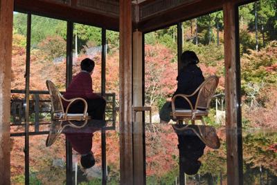 「風遊山荘」から紅葉を楽しむ行楽客。テーブルに写った逆さ風景が人気