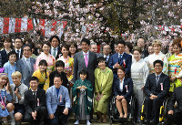 In this April 2017 file photo, Prime Minister Shinzo Abe, center left, and his wife Akie, center right, pose for photos with guests at a cherry blossom-viewing party at Shinjuku Gyoen National Garden in Tokyo's Shinjuku Ward. (Mainichi/Kimi Takeuchi)