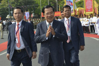 Cambodian Prime Minister Hun Sen, center, greets his government officers during the country's 66th Independence Day from France, at the Independence Monument in Phnom Penh, Cambodia, on Nov. 9, 2019. (AP Photo/Vithy Soth)