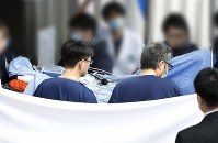 Partially processed image shows Shinji Aoba, the suspect in a deadly arson attack on a Kyoto Animation Co. studio in July, being sent back to a Kyoto hospital from one in Osaka Prefecture after undergoing multiple skin grafts. (Kyodo)