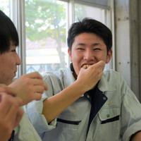 コオロギパウダーを生地に混ぜたピザを食べる菊田さん=秋田市の金足農高で