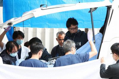 転院先の病院に到着した青葉真司容疑者をドクターカーから降ろす職員ら=14日(代表撮影)