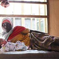 国内避難民キャンプで2時間ほど前に生まれたばかりの赤ちゃんと添い寝をするスレマン・ヤハヤ・アイシャさん(35)。8人目となる男の子は、身長52センチ、体重4900グラムと大きくて元気。「嬉しくて夫に電話した」と話した=ナイジェリア・ボルノ州マイドゥグリで2019年9月20日、山崎一輝撮影