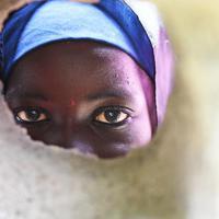 難民キャンプの壁に空いた穴から顔を覗かせる子供。このキャンプは政府非公認で教育や職業訓練などの支援はNGOが行っているが、資金や人員が不足している=マイドゥグリで2019年9月17日、山崎一輝撮影