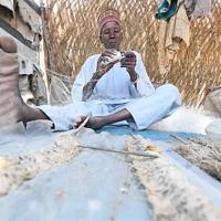 ボルノ州東部のカメルーン国境近くにある避難民キャンプで、網の手入れをする漁師のブカル・ウスマンさん(65)。チャド湖周辺に住んでいたが、近くの村がボコ・ハラムの襲撃に遭ったことから2016年に家族で避難した。子供の頃、チャド湖の岸辺は家のすぐ近くだったが、2016年には約50キロ離れた場所まで後退した。気候変動やカメルーンで建設されたダムの影響ではないかと考えている=2019年10月2日、山崎一輝撮影