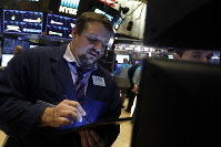 Trader Michale Milano, left, works on the floor of the New York Stock Exchange, on Nov. 14, 2019. (AP Photo/Richard Drew)
