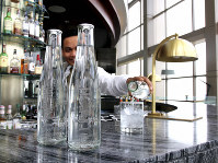 This undated image provided by Hyatt shows a water station with reusable water bottles. Hyatt Hotels Corp. is the latest hotel company to remove small bottles from its bathrooms in an effort to reduce waste. (Courtesy of Hyatt via AP)