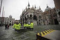 Municipal workers carry wooden boards to create a trestle bridge in a flooded St. Mark's Square in Venice, Italy on Nov. 15, 2019. (AP Photo/Luca Bruno)