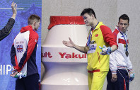 In this July 23, 2019 file photo, China's gold medalist Sun Yang gestures to Britain's bronze medalist Duncan Scott, left, following the medal ceremony in the men's 200m freestyle final at the World Swimming Championships in Gwangju, South Korea. (AP Photo/Mark Schiefelbein)