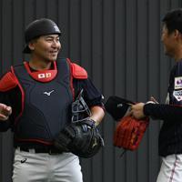 ブルペンでの投球練習後に山本(右)と言葉を交わす野球日本代表の会沢=宮崎市で2019年10月23日午前11時30分、細谷拓海撮影