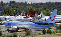 This Aug. 15, 2019, file photo shows dozens of grounded Boeing 737 MAX airplanes crowd a parking area adjacent to Boeing Field in Seattle. Boeing is settling more of the roughly 150 lawsuits filed by families of passengers killed in two crashes of the 737 Max jet. (AP Photo/Elaine Thompson, File)