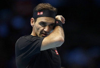 Roger Federer of Switzerland wipes his face after he plays a return to Stefanos Tsitsipas of Greece during their ATP World Tour Finals semifinal tennis match at the O2 Arena in London, Saturday, Nov. 16, 2019. (AP Photo/Kirsty Wigglesworth)