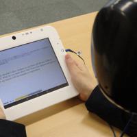 大学入学共通テストで導入予定だった英語民間試験の一つ「GTEC」のスピーキングテストの様子。受験者は外の音が聞こえないようイヤーマフをしてタブレットに向かって話す=東京都千代田区で、成田有佳撮影