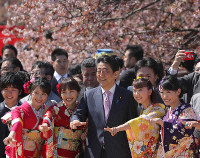 This photo taken on April 13, 2019, shows Prime Minister Shinzo Abe, center, posing with members of the Japanese idol group Momoiro Clover Z, who were invited to the annual cherry blossom-viewing party, in Tokyo's Shinjuku Ward. (Mainichi/Shinnosuke Kyan)