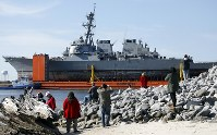 In this Jan. 19, 2018, file photo, area residents watch the transport vessel Transshelf carry the damaged USS Fitzgerald, the U.S. Navy destroyer damaged in a June 2017 collision off Japan, up the Pascagoula River in Pascagoula, Miss. (AP Photo/Rogelio V. Solis)
