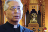In this Nov. 16, 2019, photo, Japanese Archbishop Mitsuaki Takami, who heads Nagasaki's Catholic community of 60,000, speaks in front of a statue of the Virgin Mary that was damaged in the A-bomb attack at Urakami Cathedral in Nagasaki, southern Japan. (AP Photo/Eugene Hoshiko)