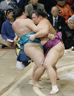 Komusubi Asanoyama, rgiht, shoves out No. 2 maegashira Meisei on Day 10 of the Kyushu Grand Sumo Tournament. (Kyodo)