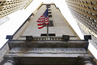 In this Nov. 13, 2015, photo, the American flag flies above the Wall Street entrance to the New York Stock Exchange, in New York. (AP Photo/Richard Drew)