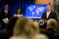Secretary of State Mike Pompeo, right, accompanied by U.S. special representative on Iran Brian Hook, left, and State Department spokeswoman Morgan Ortagus, second from left, speaks at a news conference at the State Department in Washington, on Nov. 18, 2019. (AP Photo/Andrew Harnik)