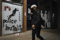 A protester walks past graffiti depicting police as a dog and various slogans including