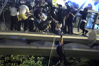 Protesters use ropes to lower themselves from a pedestrian bridge to waiting motorbikes in order to escape from Hong Kong Polytechnic University and the police in Hong Kong, Monday, Nov. 18, 2019. (AP Photo/Kin Cheung)