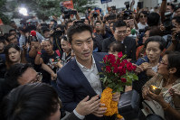 Thanathorn Juangroongruangkit, center, leader of the anti-military Future Forward Party, is surrounded by his supporters as he arrives at Constitutional Court in Bangkok, Thailand, on Nov. 20, 2019. (AP Photo/Gemunu Amarasinghe)