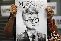 In this Aug. 21, 2019 file photo, a supporter holds a poster outside of the British Consulate in Hong Kong during a rally in support of a consulate employee who was detained while returning from a trip to China. (AP Photo/Vincent Yu)