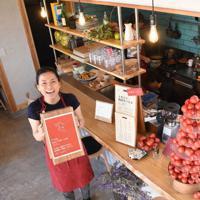 オープン初日の「Eat&Stay とまとと」。小野加央里さん(左)が1階の厨房前で笑顔を見せる=日高村で、郡悠介撮影