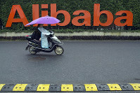 In this May 27, 2016, file photo, a woman rides a bike past the company logo outside the Alibaba Group headquarters in Hangzhou, in eastern China's Zhejiang province. (AP Photo/Ng Han Guan)