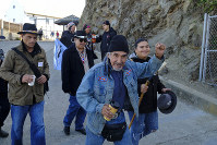 Eloy Martinez, who took part in the Native American occupation, raises a fist while making his way to ceremonies marking the 50th anniversary of the occupation on Alcatraz Island, on Nov. 20, 2019, in San Francisco. (AP Photo/Eric Risberg)