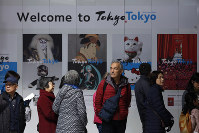 Tourists stand in front of a