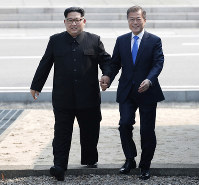 In this April 27, 2018 file photo, North Korean leader Kim Jong Un, left, and South Korean President Moon Jae-in cross the military demarcation line to the South side at the border village of Panmunjom in the Demilitarized Zone. (Korea Summit Press Pool via AP)