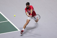 Serbia's Novak Djokovic returns the ball to Japan's Yoshihito Nishioka during their Davis Cup tennis match in Madrid, Spain, on  Nov. 20, 2019. (AP Photo/Manu Fernandez)
