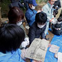 約35年ぶりにタイムカプセルをほりだし、埋めた日の新聞朝刊を手にとる卒業生たち=福島県双葉町で2019年11月22日午前11時31分、和田大典撮影