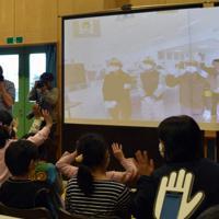 双葉町内から中継でつないだ除染作業の関係者に子供たちは手を振りました