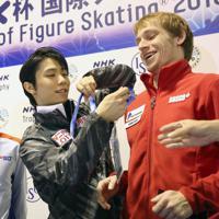 【NHK杯フィギュア】男子SP後の記者会見を前に、3位につけたロシアのセルゲイ・ボロノフ(右)のIDカードを取ってあげる羽生結弦=真駒内セキスイハイムアイスアリーナで2019年11月22日、貝塚太一撮影