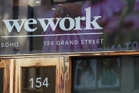 This Oct. 15, 2019, file photo shows a WeWork logo at the entrance to one of their office spaces in the SoHo neighborhood of New York. (AP Photo/Mary Altaffer)
