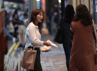 In this Nov. 7, 2019 photo, district council candidate Cathy Yau distributes flyers to pedestrians during her campaign at Causeway Bay in Hong Kong. Yau, a former police officer, grew exasperated as police used more force to quell the unrest. She quit the force in July after 11 years, and is running in Sunday's district polls. (AP Photo/Dita Alangkara)