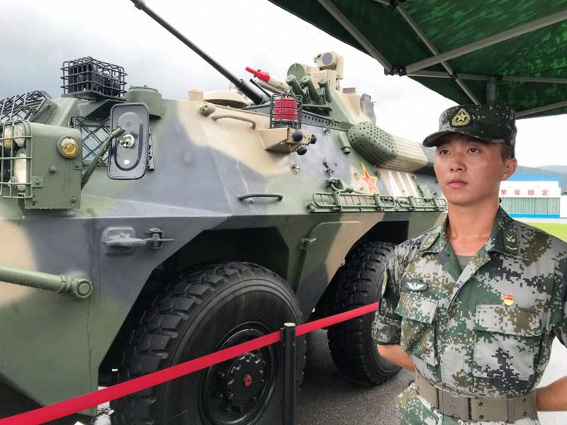 展示された戦車の前に立つ人民解放軍の兵士=香港・石崗基地で2019年6月29日、福岡静哉撮影