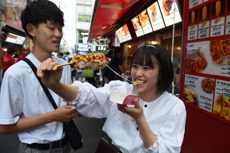 伸びるチーズが「インスタ映え」するとして人気があるチーズドッグ「ハットグ」を食べる若者=東京・新大久保で2019年7月18日午後4時20分、北山夏帆撮影