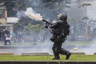A police officer fires tear gas at anti-government protesters in Bogota, Colombia, on Nov. 21, 2019. (AP Photo/Ivan Valencia)