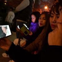 元安川沿いに座り、「平和のための集い」の中継映像を見る人たち=広島市中区で2019年11月24日午後7時11分、小松雄介撮影