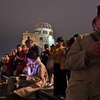 原爆ドームのそばに座り、「平和のための集い」の中継映像を見る人たち=広島市中区で2019年11月24日午後7時24分、小松雄介撮影