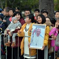 肖像写真を手にフランシスコ・ローマ教皇の到着を待つ人たち=広島市中区で2019年11月24日午後4時52分、小松雄介撮影
