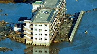 東日本大震災で、海水に覆われたマンションの屋上で救助を待つ人たち=宮城県南三陸町で2011年3月12日午後4時28分、本社機から貝塚太一撮影