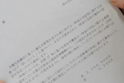 佐藤さんが見つめた認定決定通知書=山形県鶴岡市で