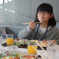 機内食風のランチをおいしそうに食べる参加した子ども=千葉県成田市で
