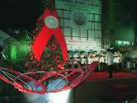 「世界エイズデーイベント」で点灯された「レッドリボンツリー」=東京・JR新宿駅東口で1999年